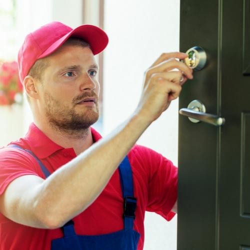 handyman in red uniform fixing house door lock